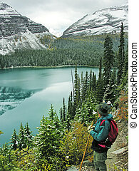 Hiker admiring Lake O'Hara, Yoho National Park, Canada -...