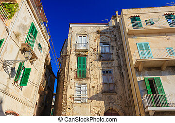 Tropea architecture with typical green shutters and yellow...
