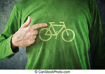 Man pointing to bicycle insignia printed on his green shirt,...