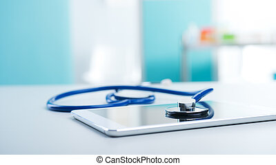 Medical equipment: blue stethoscope and a digital tablet.