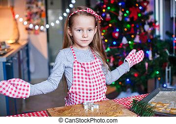 Happy little girl in wore mittens baking Christmas...