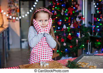 Adorable little girl in wore mittens baking Christmas...