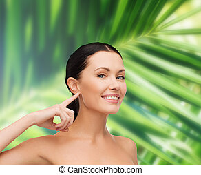 young calm woman pointing to her ear - health, spa and...