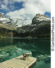 Chair on a wooden pier, Lake O'Hara, Yoho National Park,...