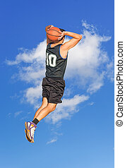 dunking in the sky - basketball player dunking with a blue...