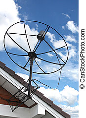 Satellite dish Stuck to roof of house on Blue sky. - The...