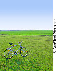 Bicycle in green 1 - Modern bicycle in green field on clear...