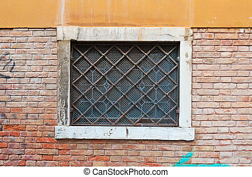 grilled window - old grilled window in a brick wall in...
