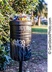 Litter - an overfilled and vandalized trash can in a park