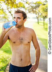 Man drinking water after workout outdoors - Portrait of...