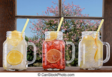 Summer Drinks - Glasses of lemonade and fruit juice on a...
