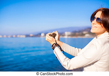 Woman hands holding small stones form heart shape background the sea
