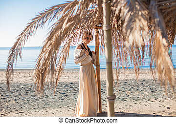 Adorable young woman in a beautiful dress on the beach