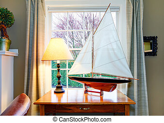 Classic living room with a wonderfully matched handicraft soalboat on rustic wooden table