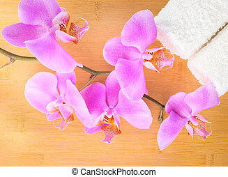 branch lilac orchid and white towels on bamboo wooden...