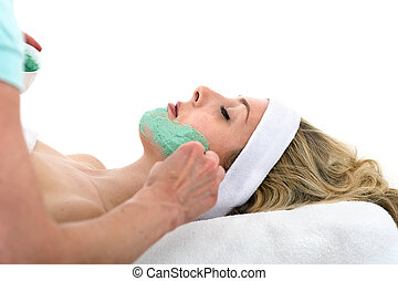 Beautician applying facial mask on beautiful woman.