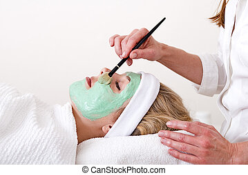 Beautician applying facial mask on the cheekbones.