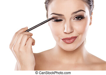 make up - Woman applying eyeshadow