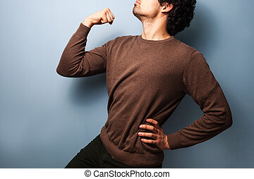 Young man in proud stance with fist raised