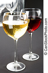 Glasses of red and white wine on grey background Space for...