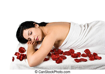 Spa massage - Young woman lying on a massage table with rose...