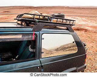 In the desert - a small dirty car parked in the sahara...