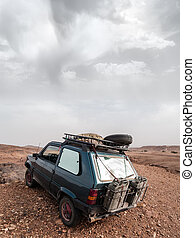 Adventure - a dirty and small 4x4 car parked in the sahara...