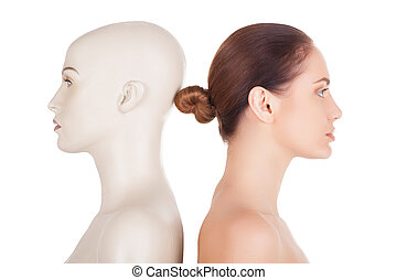Real and artificial. Side view of beautiful young shirtless woman standing her back to the mannequin and looking away while isolated on white background