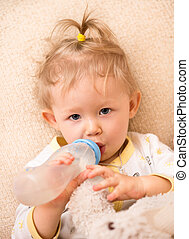 Child girl with bottle with infant formula at home.The...
