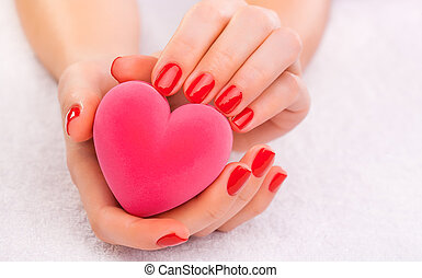 red manicure with gift box on the white towel - Closeup red...