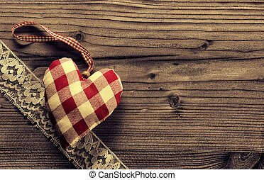 Checked fabric heart with lace wood background