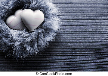 Heart-shaped chocolates in nest, wood background