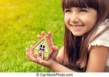 portrait of a pretty little girl with house in hand on a background of green grass