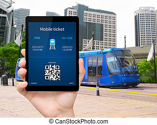 man hand holding the tablet with a mobile wallet and train ticket against the blue train in the city