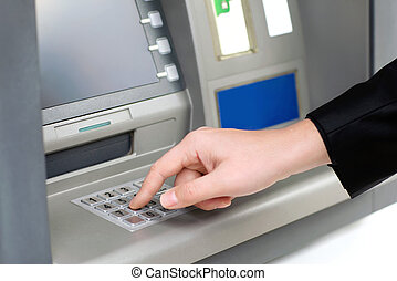 man enters a PIN code and withdraws money from an ATM