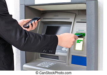 businessman inserts a credit card into the ATM to withdraw...