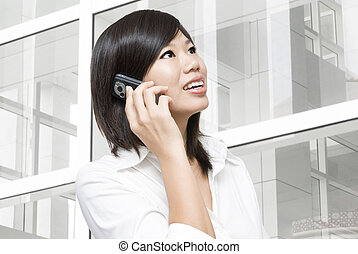 Asian business woman on the phone at modern building