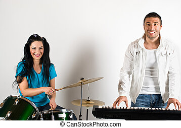 Happy musical band with man and woman playing drums and...