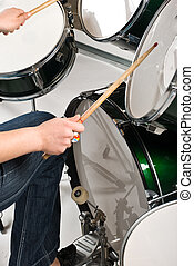 Playing drums - Part of woman legs on drum pedal holding...