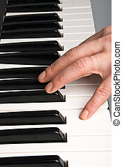 Piano keyboard - Human hand playing piano keyboard or...