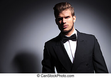 handsome man in tuxedo and bow tie in a dramatic pose