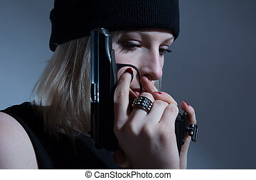 Young girl in a dark cap with a gun in his hand