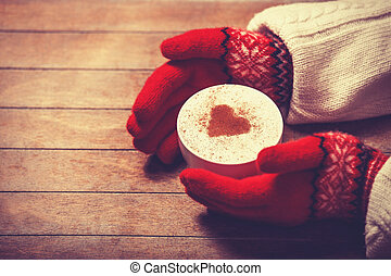 Hands in mittens holding hot cup of coffee. Photo in old...