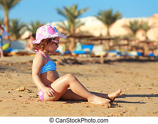 Kid girl sitting on the beach sand and sunbathing