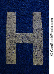 Letter H - Alphabet letter H in yellow paint on pavement