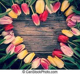 Empty heart-shaped frame of fresh tulips