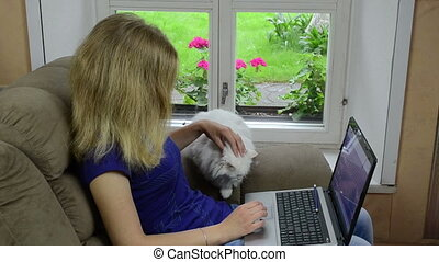 woman laptop cat armchair - Blond woman sitting on armchair...