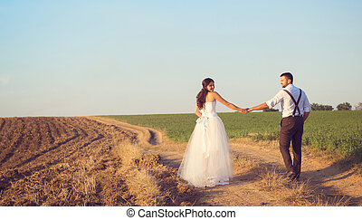 Wedding walk - Wedding couple walking in a field under the...