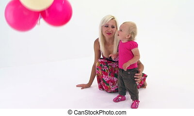 Playing with balloons - Mother and daughter playing with...