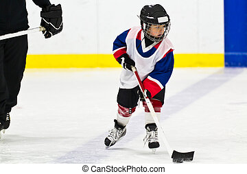 Child skating with a puck at ice hockey practice